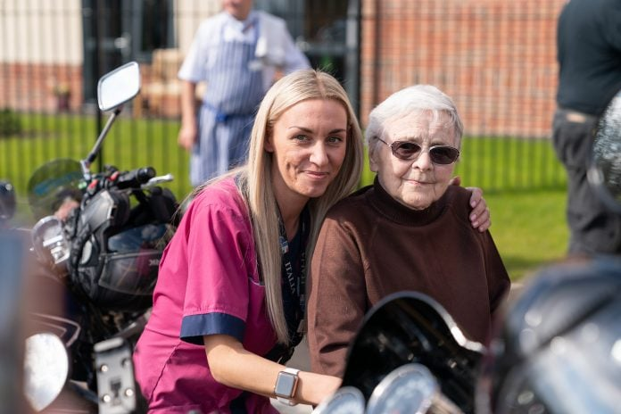 New Cares activities coordinator Amy Simpson left with Dorothy Stapleton right who was reliving her youth on a motorbike