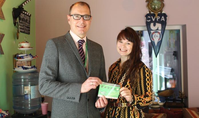 Rushcliffe Borough Councils Executive Manager Dave Banks presents Michaela from Fuzzy Panda with the top rating window sticker